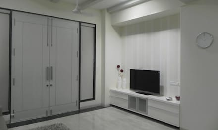 Storage aligned with the TV:  Electronics by Chawla N Associates