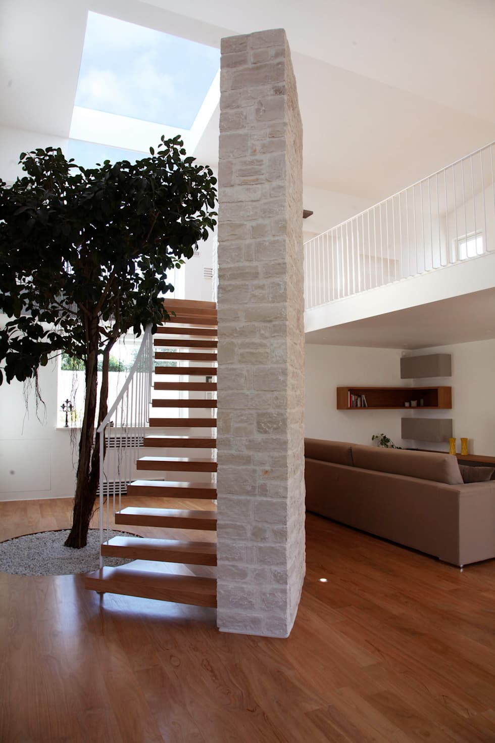 un albero in casa: Case in stile in stile Mediterraneo di m12 architettura design