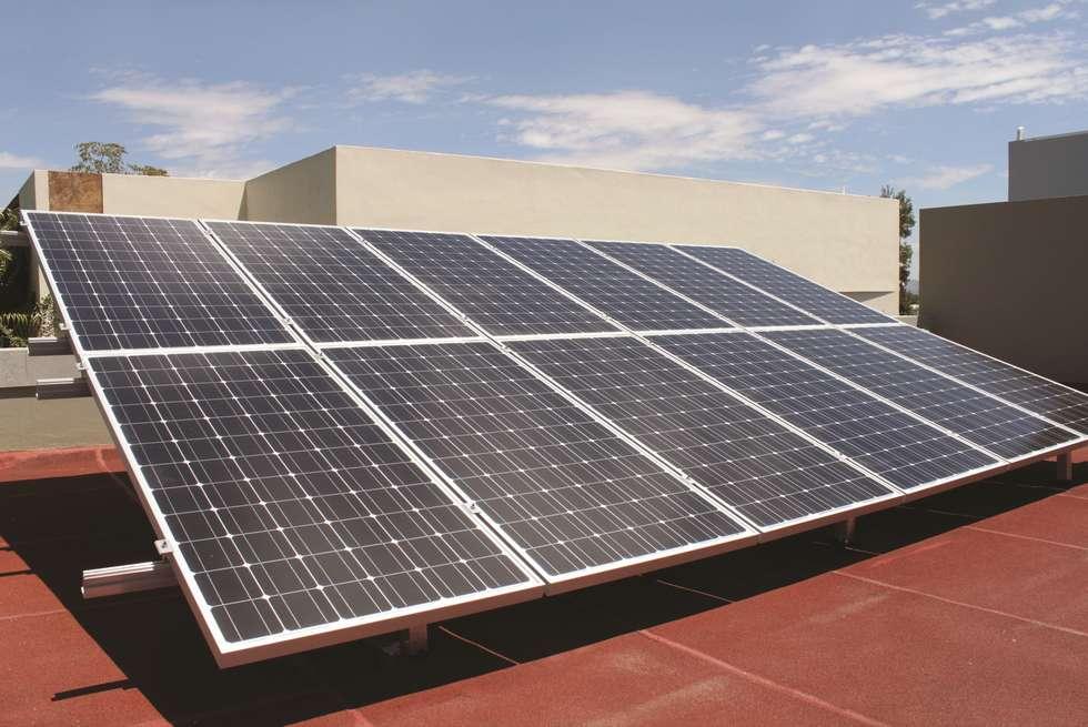 paneles solares fotovoltaicos.: Casas de estilo minimalista por Excelencia en Diseño
