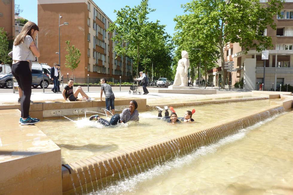 La fontaine fait la joie des petits et grands les jours de beau temps: Lieux d'événements de style  par atelier VILLES & PAYSAGES