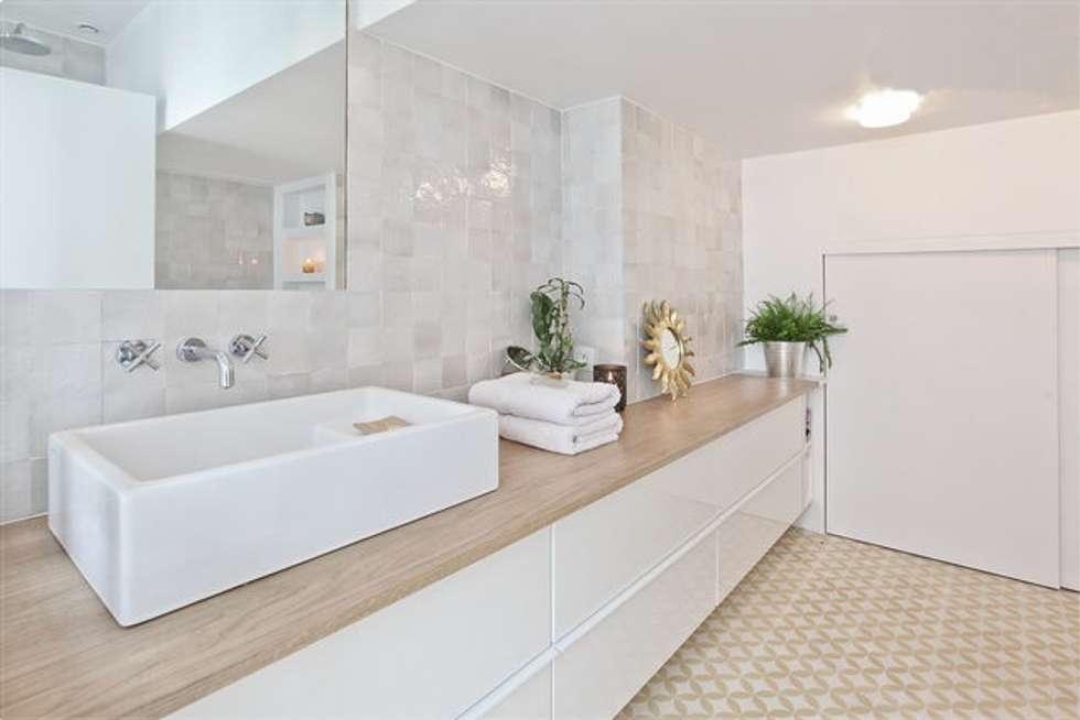 Duplex sur le canal: Salle de bains de style  par Atelier UOA