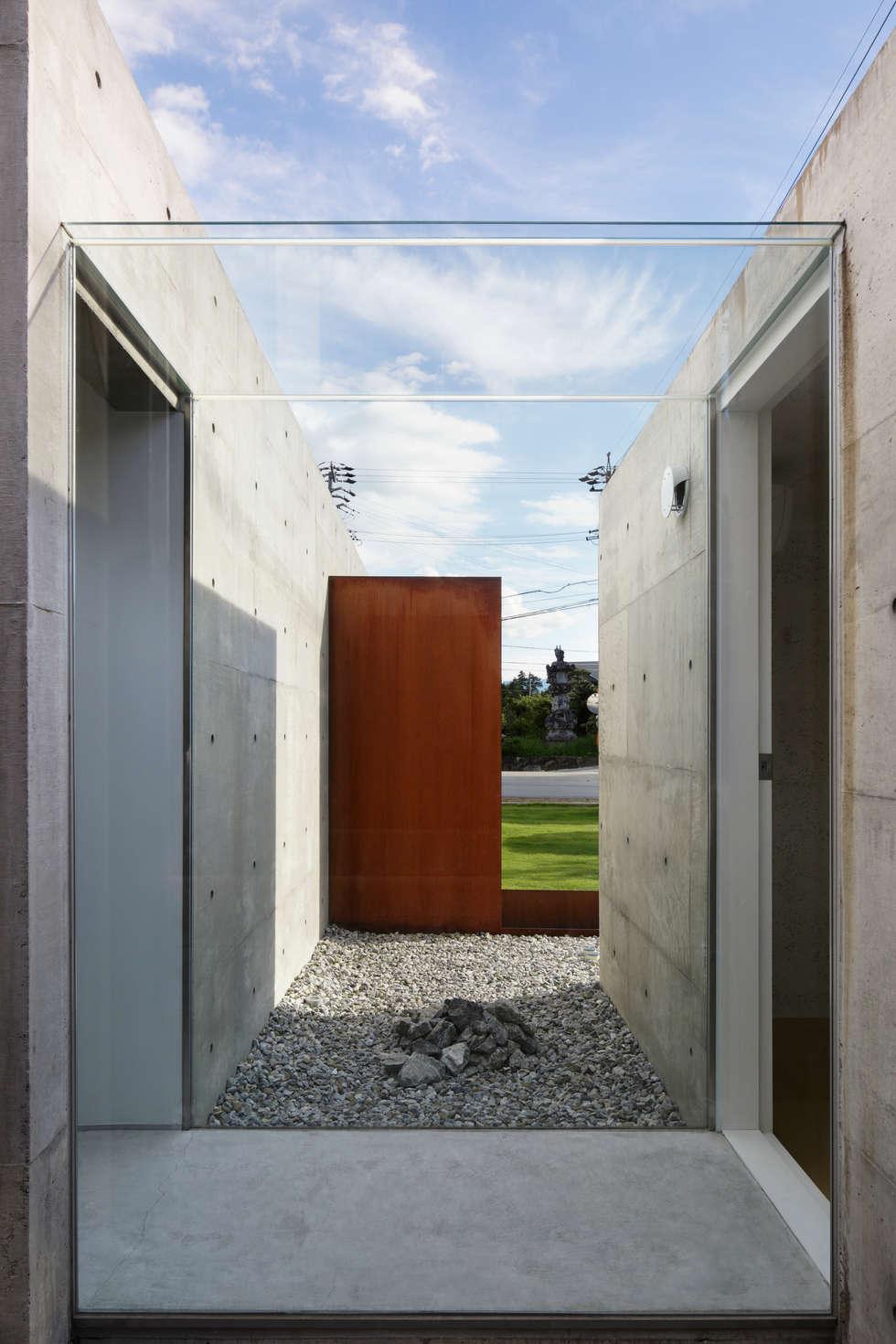 ガラスの回廊と石庭: TNdesign一級建築士事務所が手掛けた家です。