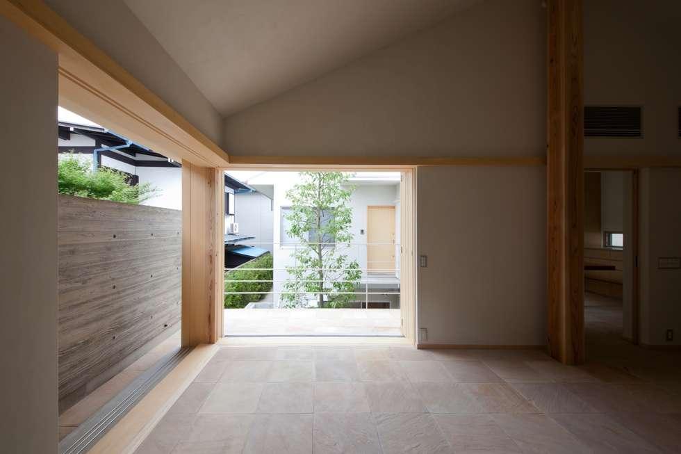 全開できる木製サッシを開け放すと中庭と一体になるリビング!: 根岸達己建築室が手掛けたリビングです。