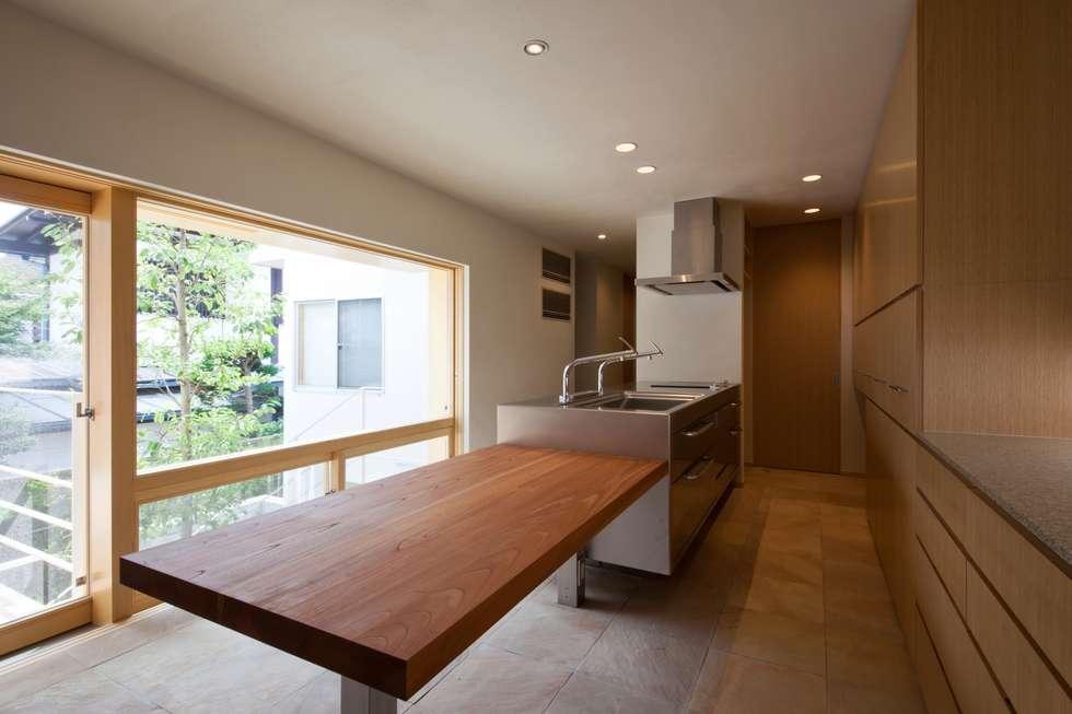 中庭の緑を見ながら家事ができるキッチン: 根岸達己建築室が手掛けたキッチンです。