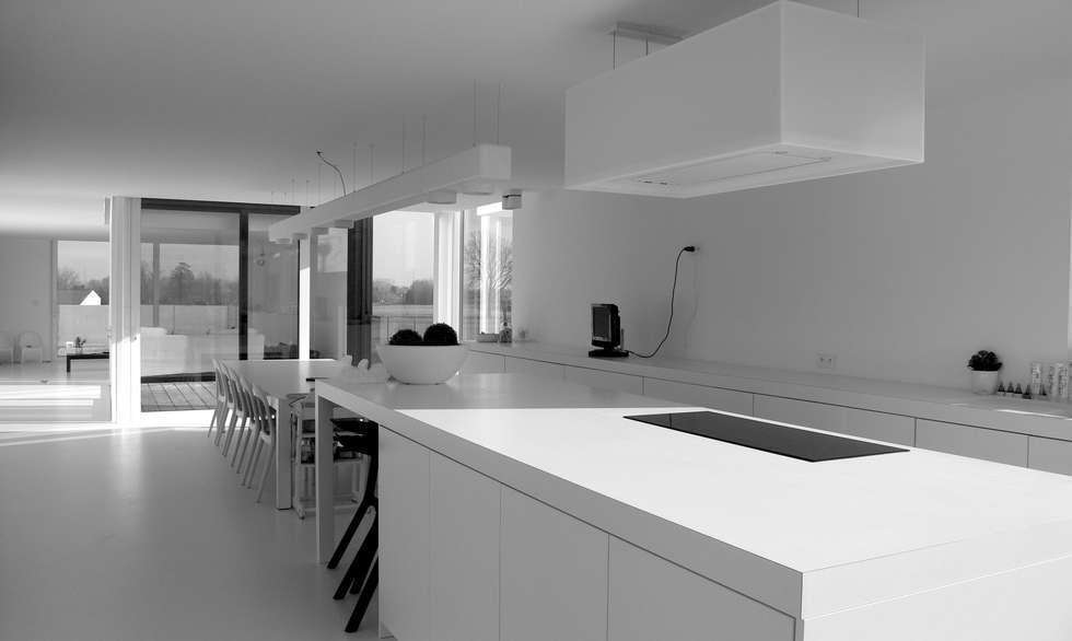 Zicht vanuit keuken op eetplaats en middagterras.: minimalistische Keuken door aHa-architecten gcv