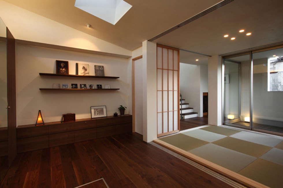 ファミリーポートレイト 寝室から和室方面: アーキシップス古前建築設計事務所が手掛けた寝室です。