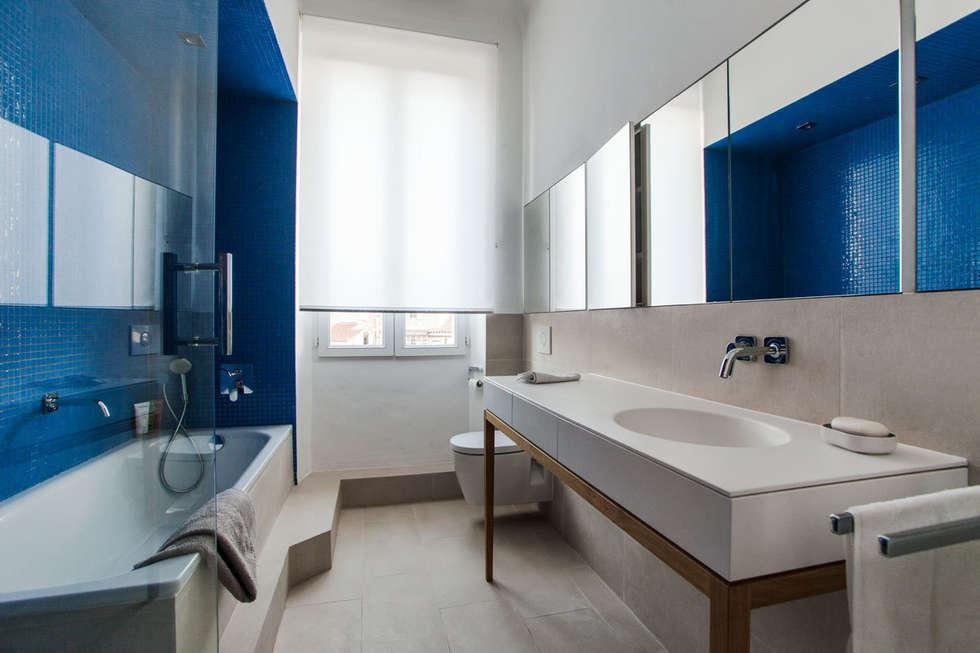 Le revêtement en carrelage beige de la marche, du sol et du mur permet d'unifier l'espace de manière douce.: Salle de bains de style  par Charlotte Raynaud Studio