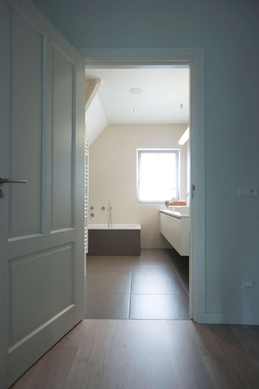 Doorkijk van de gang naar de badkamer: moderne Badkamer door Hemels Wonen interieuradvies en ontwerp