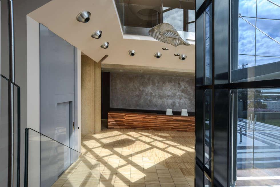Ingresso con bancone ricevimento: Ingresso & Corridoio in stile  di Studio Merlini Architectural Concept