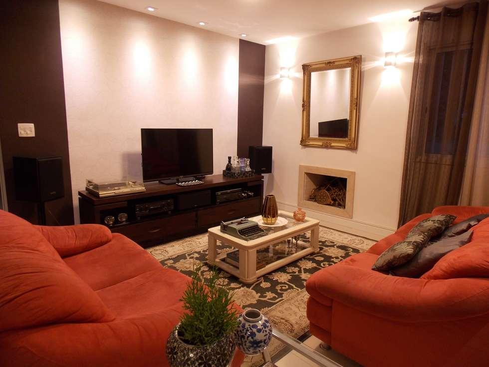 Sala aconchegante com sofás vermelhos: Salas de estar ecléticas por Lúcia Vale Interiores