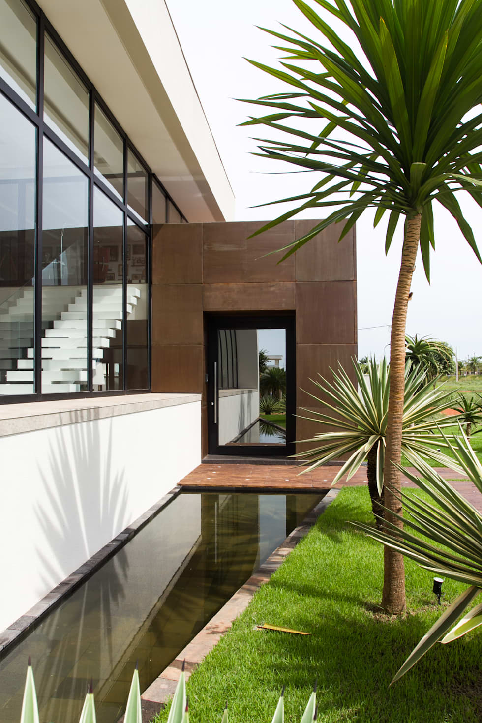 A porta de entrada reflete a paisagem: Casas minimalistas por RABAIOLI I FREITAS