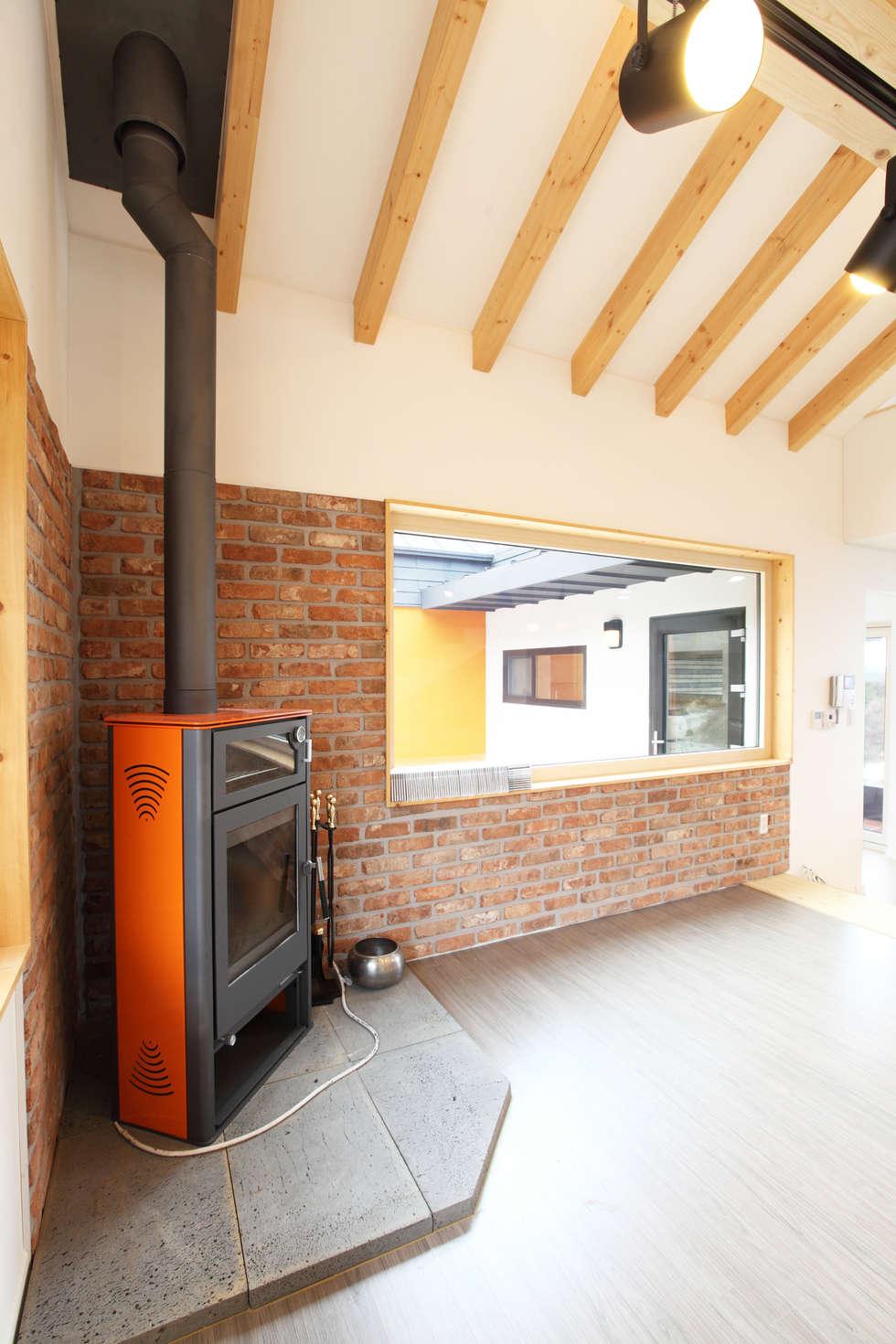 벽난로가 있는 거실: 주택설계전문 디자인그룹 홈스타일토토의  거실