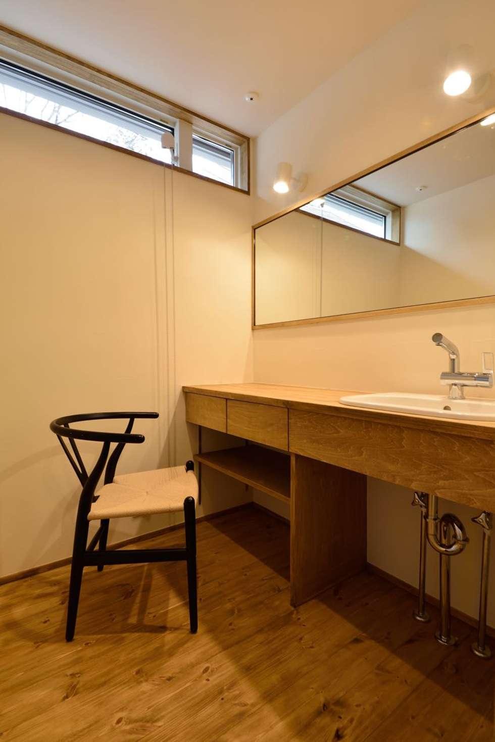 洗面所の鏡: アトリエdoor一級建築士事務所が手掛けた浴室です。