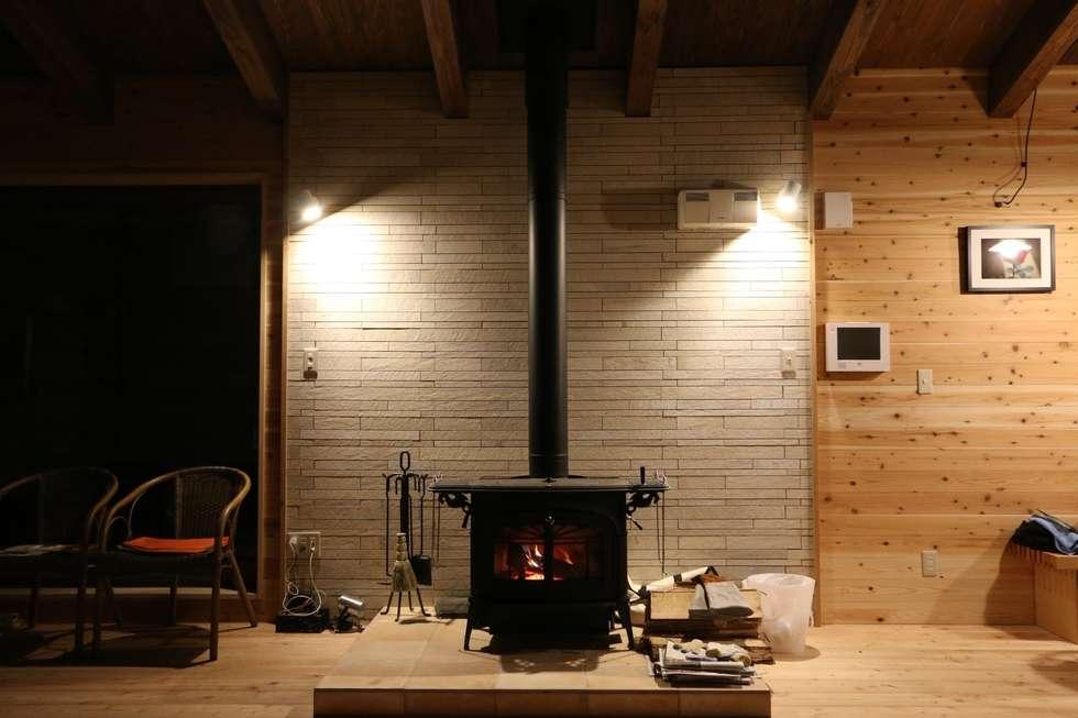 住まいの中心の薪ストーブ: 一級建築士事務所 クレアシオン・アーキテクツが手掛けたリビングルームです。