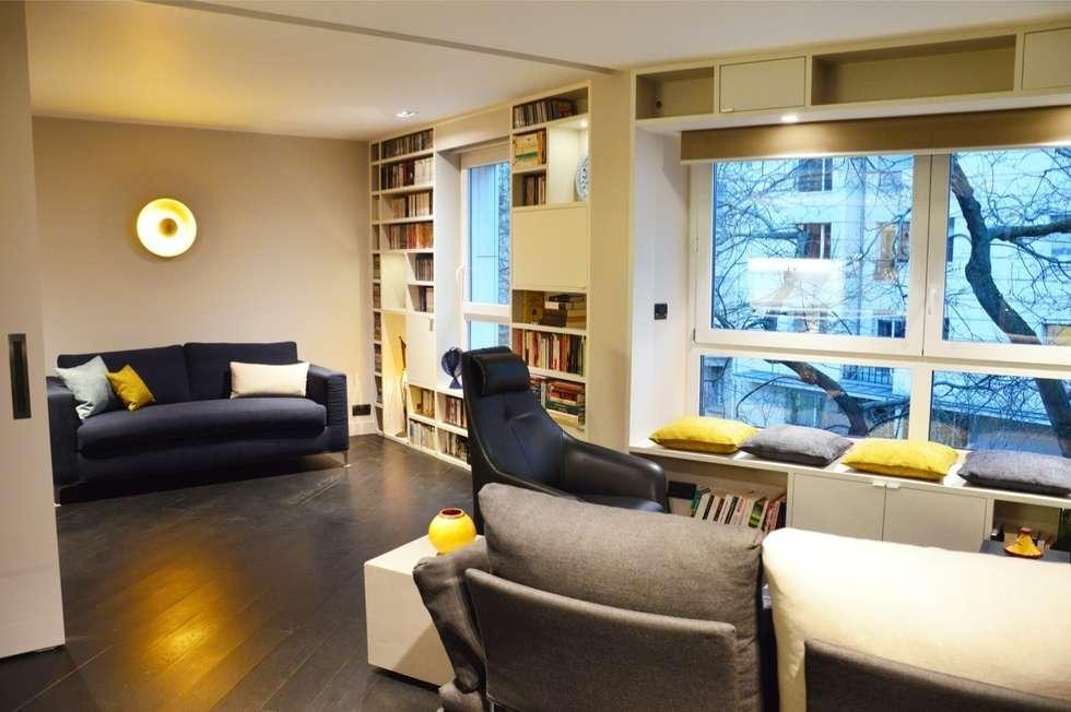 Salon avec une bibliothèque sur façade et une porte coulissante télescopique pour séparer les espaces: Salon de style de style Moderne par Agence MIND