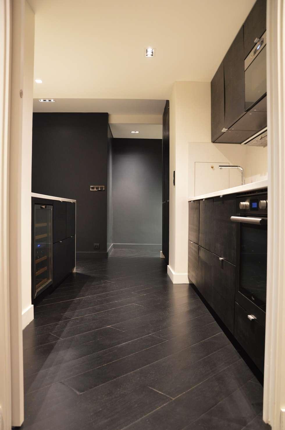 Cuisine ouverte tout en chêne teinté noir, sol et meuble, et quartz aspect marbre blanc: Cuisine de style de style Moderne par Agence MIND