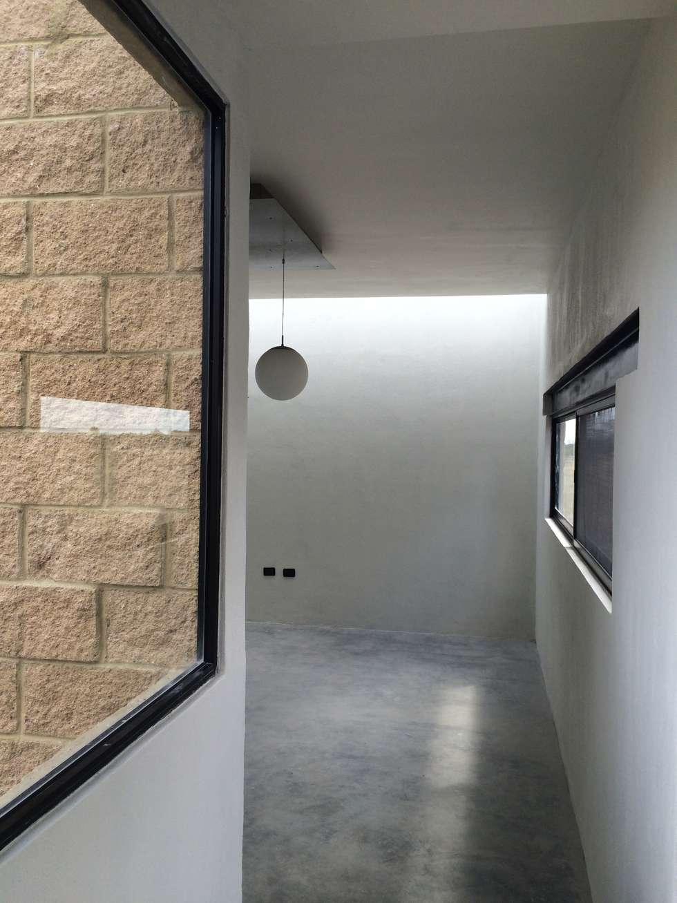 Sala con iluminación cenital, acabados claros y piso de concreto.: Salas de estilo rural por Paramétrica Arquitectos