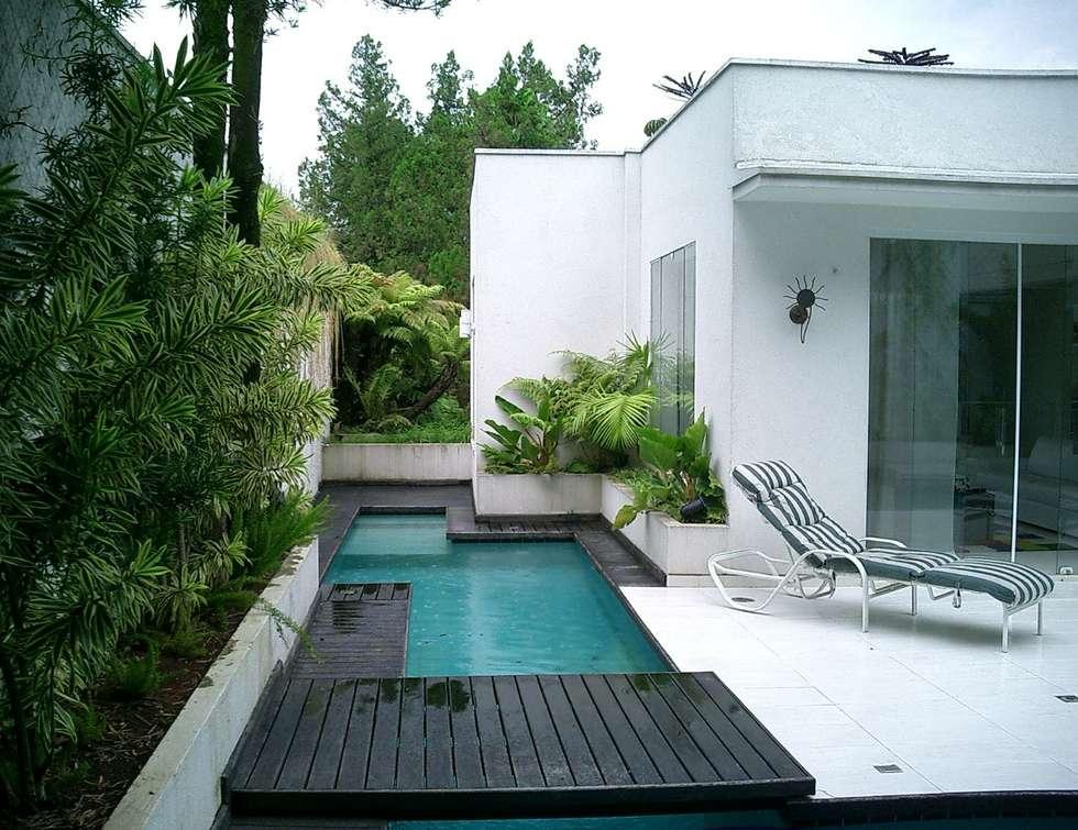 Casa minimalista na metrópole: Piscinas tropicais por Kika Prata Arquitetura e Interiores.