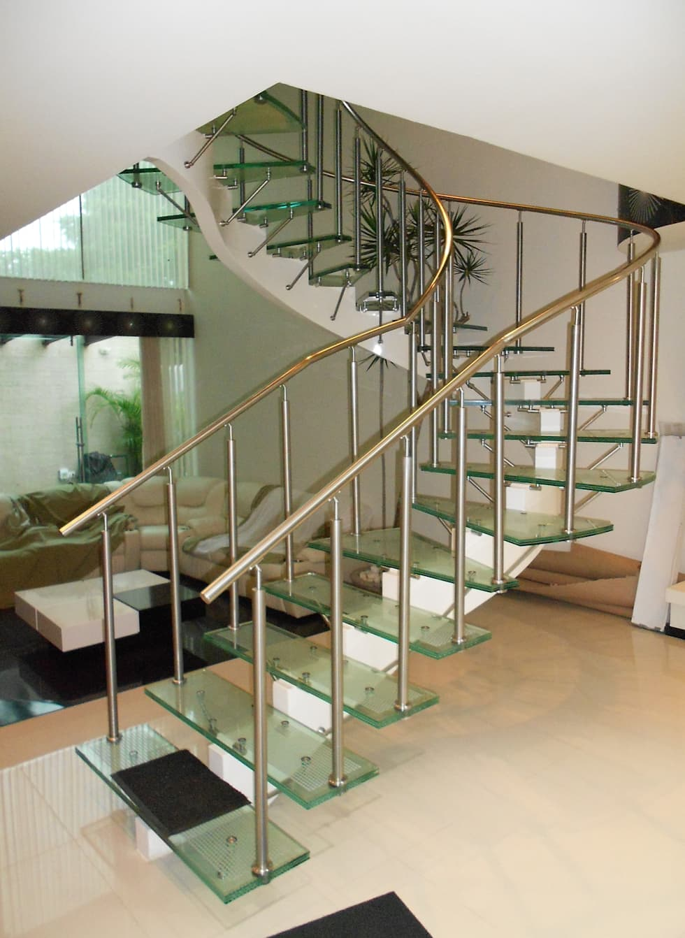 escalera de cristal laminado con pasamanos y herrajes de acero inoxidable vista pasillo ue