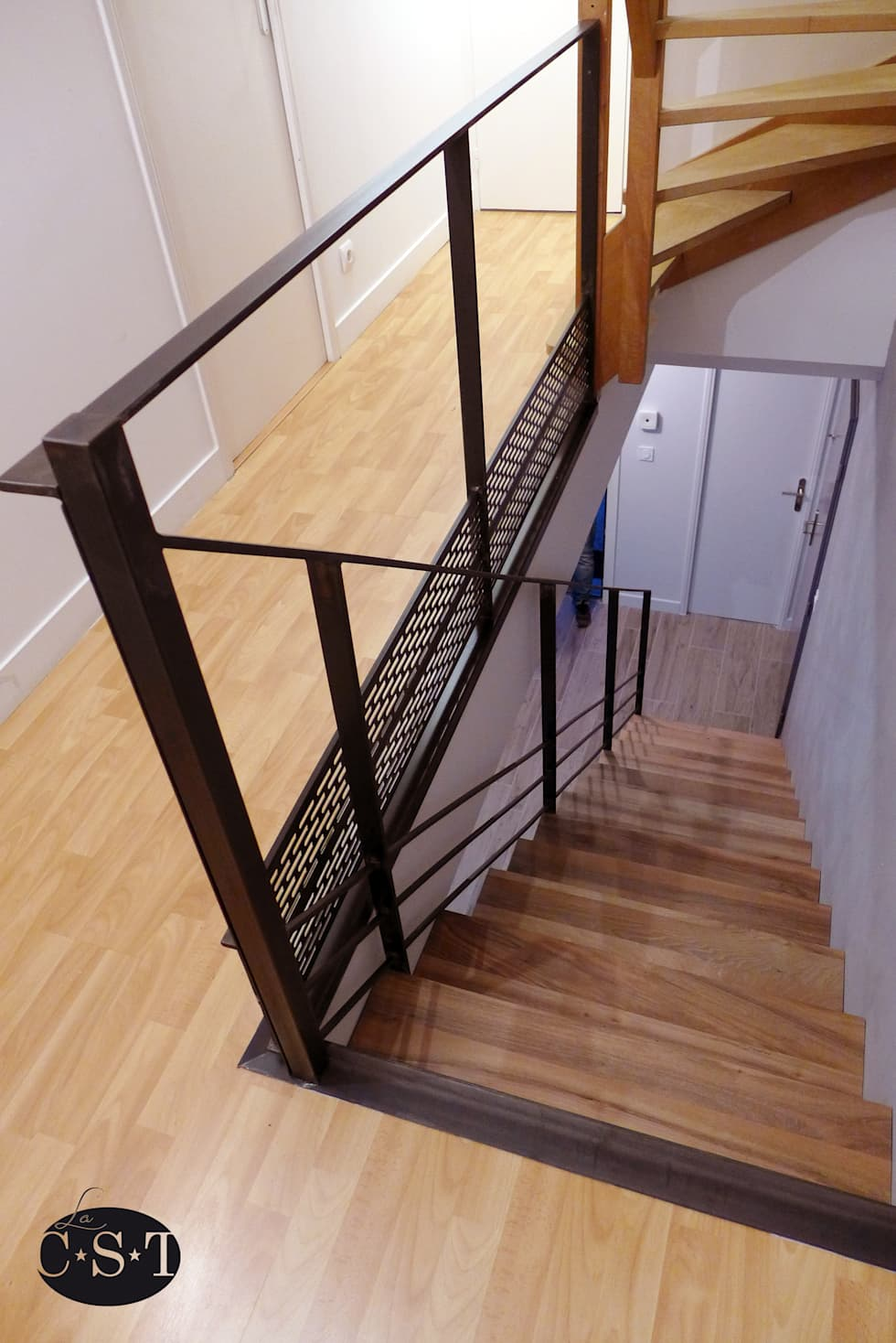 Acier et bois: un escalier sans limon apparent: Couloir et hall d'entrée de style  par La C.S.T