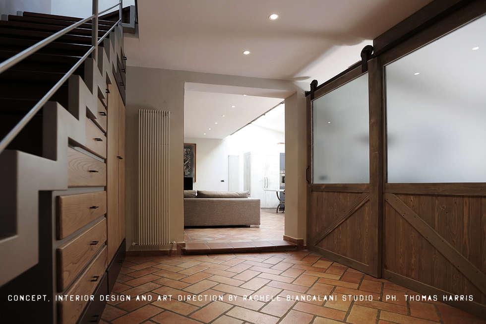 Entrance and the double slidign BARN doors designed by Rachele Biancalani: Spogliatoio in stile  di Rachele Biancalani Studio - Architecture & Design