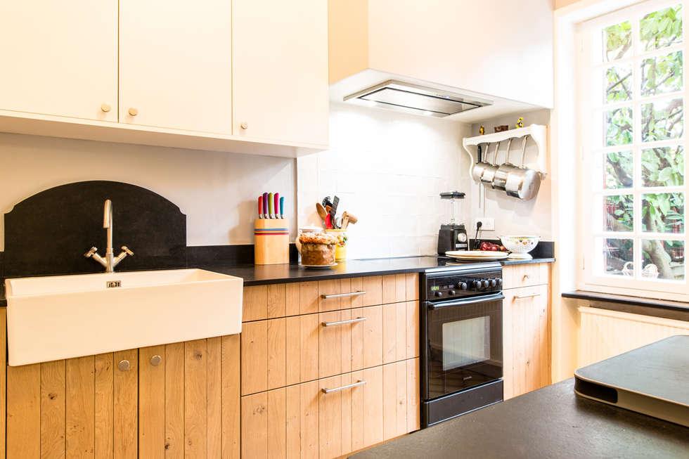 Cuisine évolution en chêne massif huilé et son plan de travail en granit noir: Cuisine de style de style Classique par MJ Home