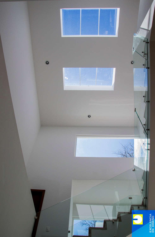 escalera : Pasillos y recibidores de estilo  por Excelencia en Diseño