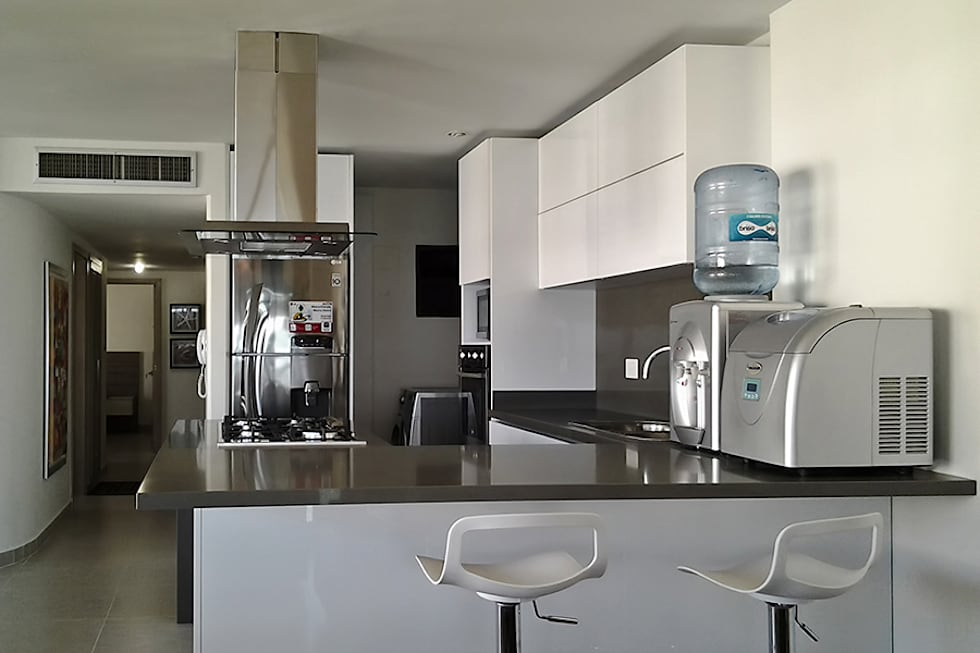 Vista de la cocina hacia el hall de alcobas: Cocinas de estilo moderno por Remodelar Proyectos Integrales