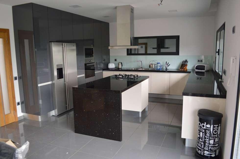 Cozinha com ilha, colunas, forra de vidro e electrodomésticos encastrados: Cozinhas modernas por Ansidecor