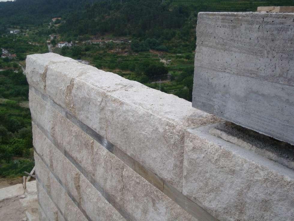 Pormenor da parede de granito: Casas modernas por Área77 - arquitectura, engenharia e design, lda