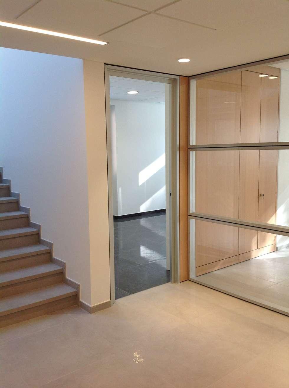 PALAZZINA UFFICI: Ingresso & Corridoio in stile  di squaremeter di chiara zocchi ed erika piacentino