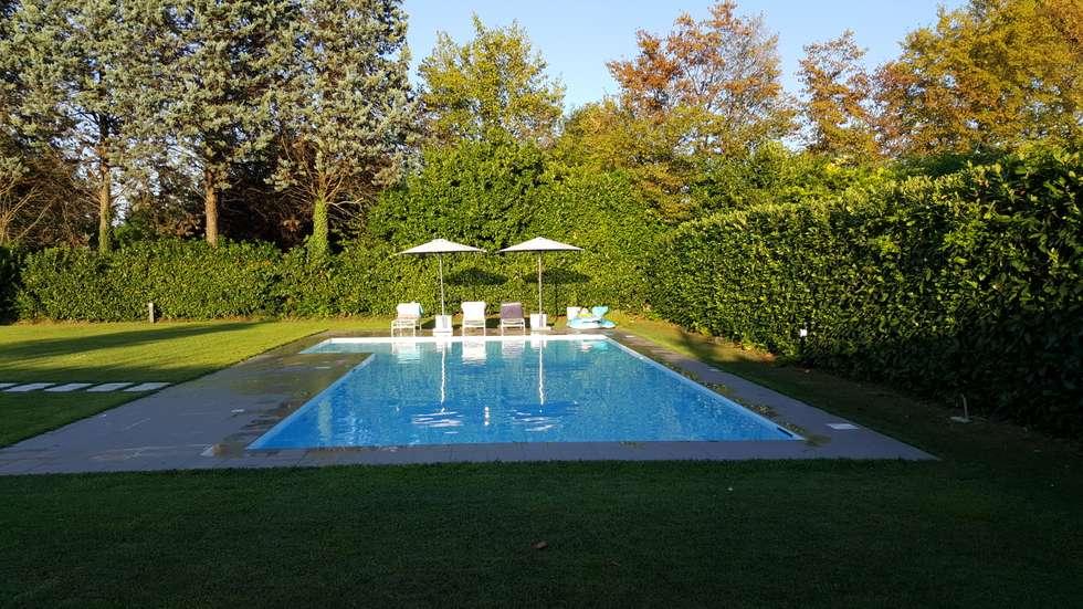 Piscina in calcestruzzo e rivestimento in gres lucido bianco: Piscina in stile in stile Moderno di iPOOL -Italian Pool Master