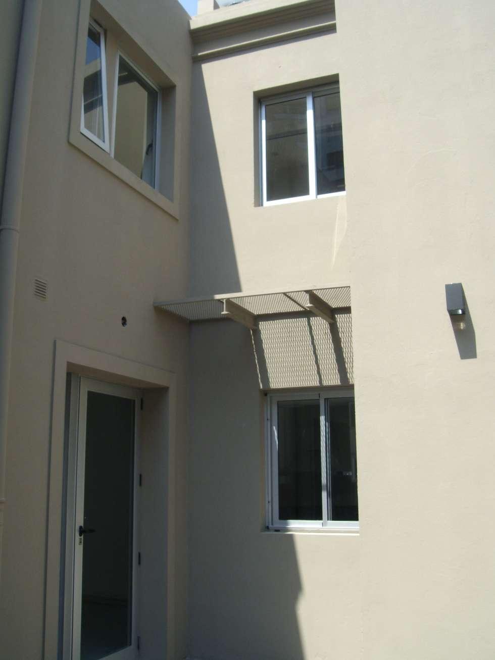 Fachada. Acceso desde el patio : Casas unifamiliares de estilo  por NG Estudio