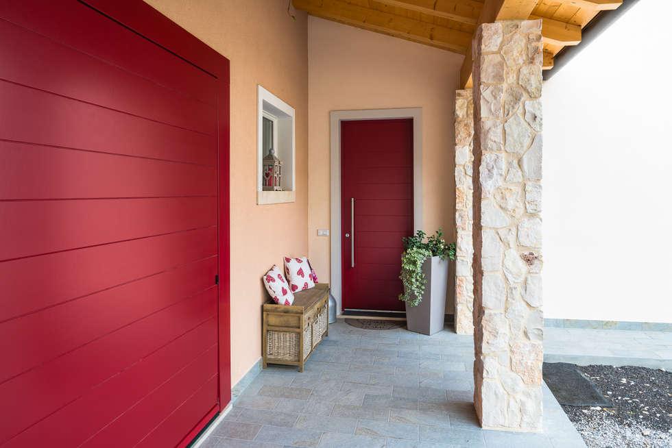 Stile collinare: Porte d'ingresso in stile  di Woodbau Srl