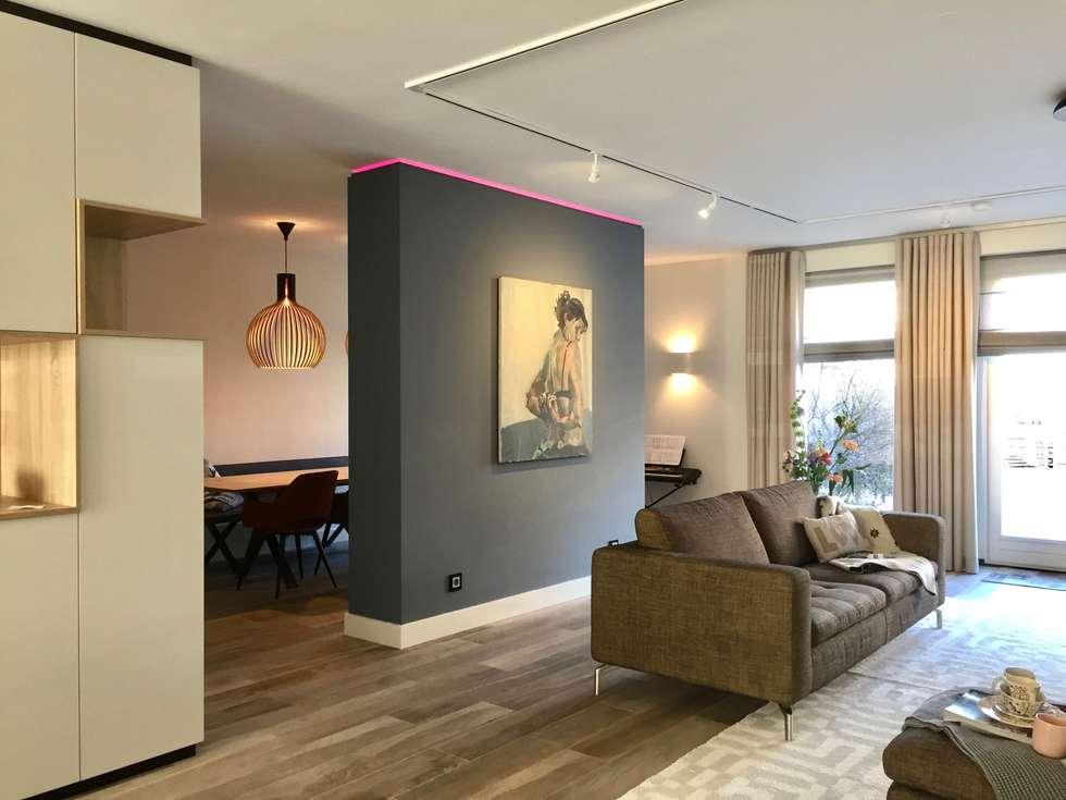 Moderne woonkamer met scheidingswand en hoekkast op maat: moderne ...