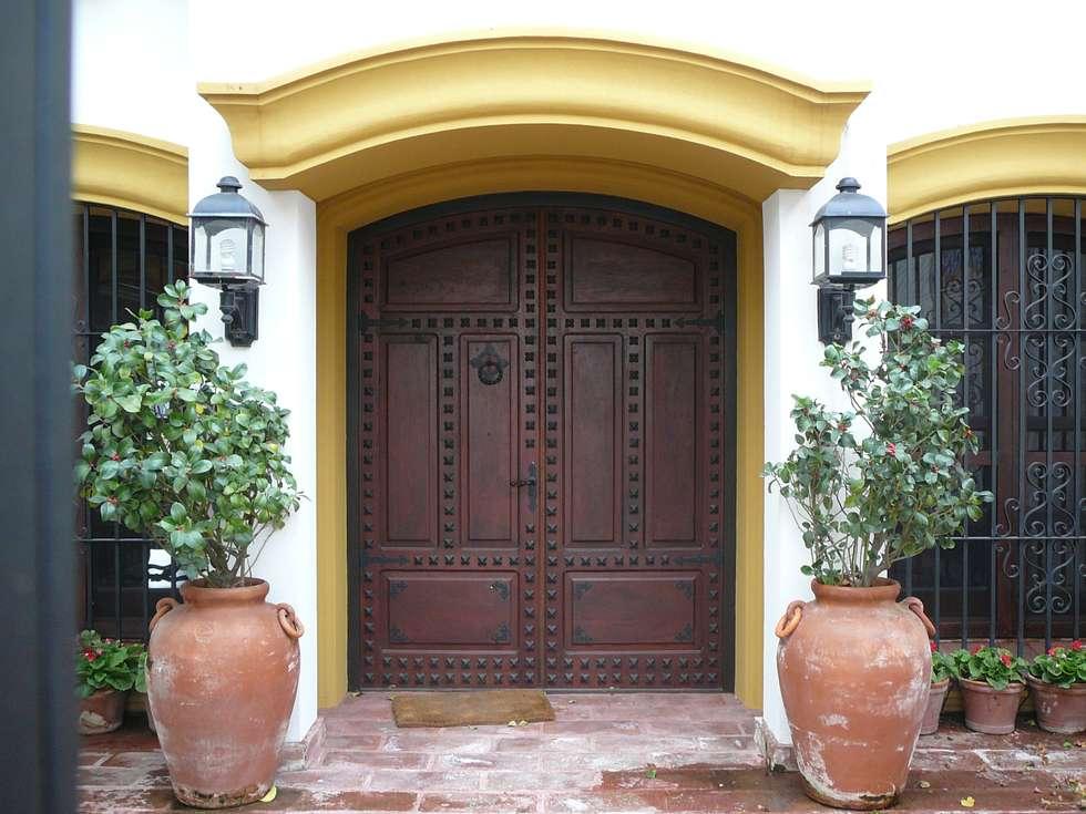 PUERTA DE ENTRADA CON DETALLES EN HIERRO: Puertas de entrada de estilo  por Estudio Dillon Terzaghi Arquitectura