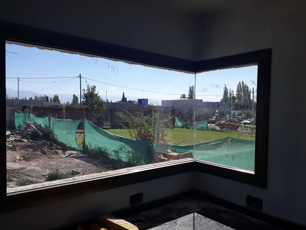 """CARPINTERIA DE ALUMINIO MEDIA Y ALTA PRESTACION CON DVH. """"UNICA EMPRESA QUE HA DESARROLADO DOBLE VIDRIADO HERMETICO (DVH CONITINUO) EN UNA VENTANA ESQUINERA"""": Ventanas de PVC de estilo  por M.i. arquitectura & construcción"""