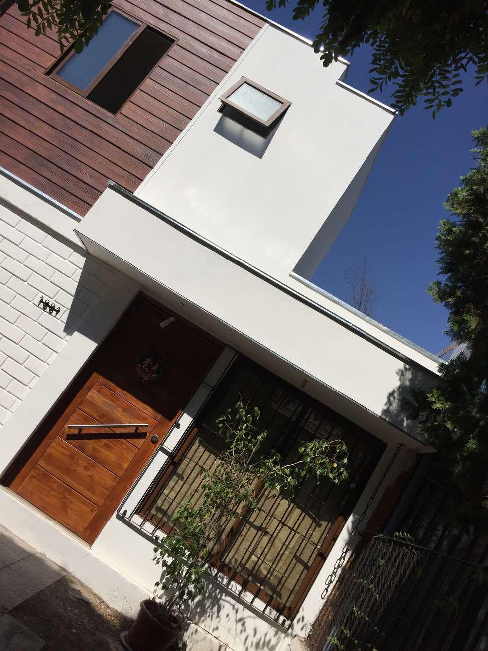 puerta acceso con protección : Casas unifamiliares de estilo  por Arqsol