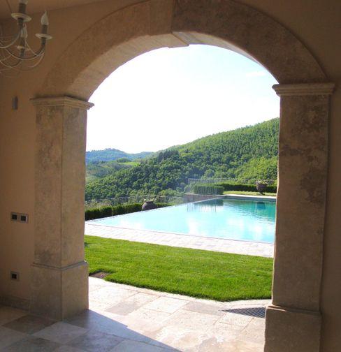 Arco in pietra, piscina a sfioro. Garden House Lazzerini Giardino classico Marmo Ambra/Oro