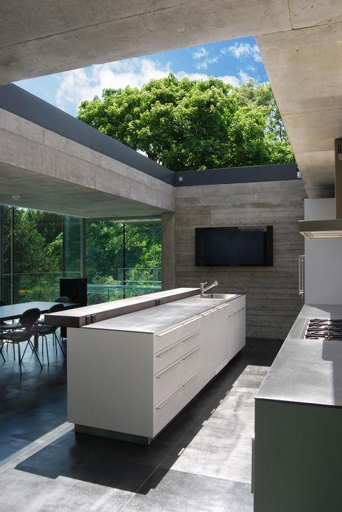 Kitchen with sliding rooflight to create open-air court Eldridge London Minimalist kitchen
