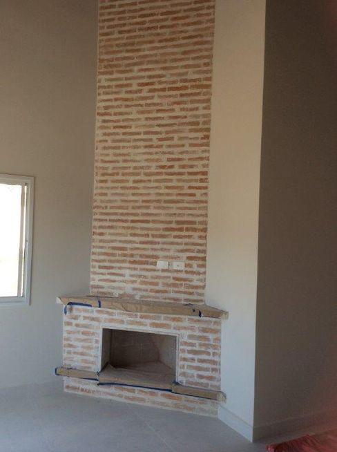 Lareira decorada em tijolos de barro Vanda Carobrezzi - Design de Interiores Salas de estar rústicas