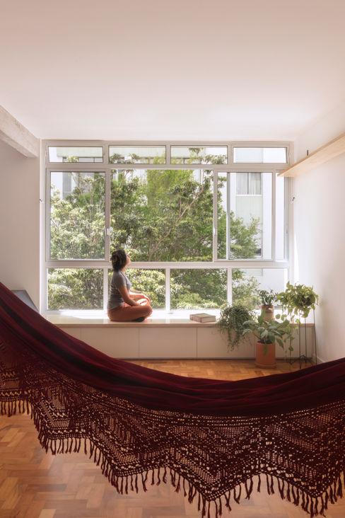 Nas árvores: janela grande em apê aconchegante com rede e plantinhas INÁ Arquitetura Salas de estar modernas
