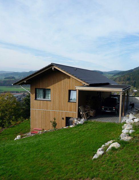 Ferienhaus mit Holzfassade und Carport Wiese und Heckmann GmbH Fertighaus Holz Braun