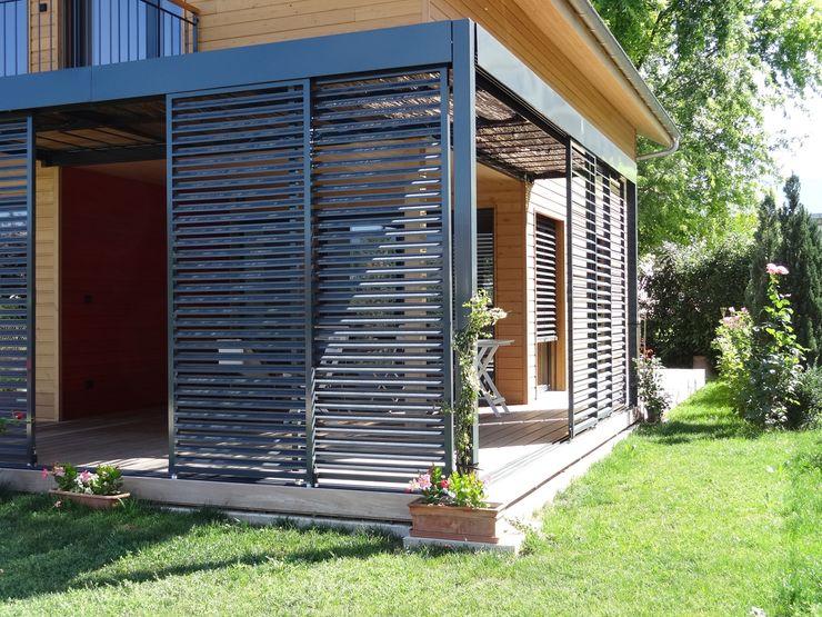Panneaux coulissants brise-soleil de la terrasse Tangentes Architectes Maisons modernes
