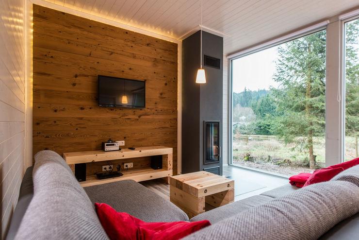 Ein schlanker Kamin und der rustikale Holzspiegel garantieren gemütliche Abende im Kreise Ihrer Lieben Ferienhaus Lichtung im grünen Herzen Deutschland Skandinavische Wohnzimmer