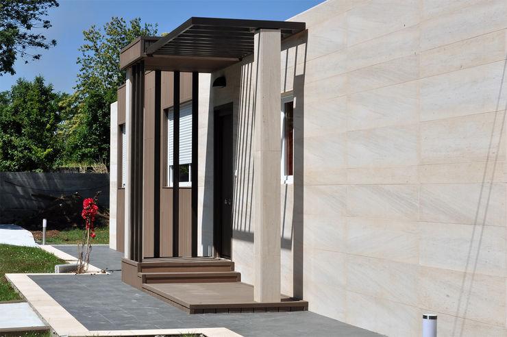 Fachada y porche delanteros en una casa Cube de 100 metros cuadrados Casas Cube Casas modernas: Ideas, imágenes y decoración