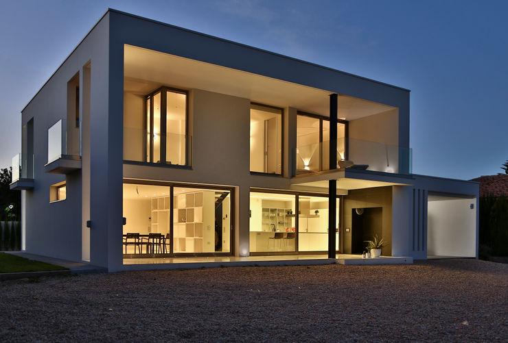 Fachada de la casa de hormigón y vidrio homify Casas unifamiliares Concreto Blanco