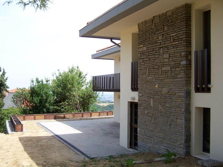 Il grande camino originario trattato esternamente in materiale lapideo. Simona Muzzi Architetto Pareti & Pavimenti in stile moderno