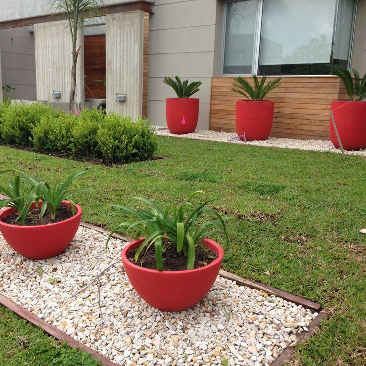 un jardin moderno con grandes macetas rojas BAIRES GREEN Jardines de estilo moderno Rojo