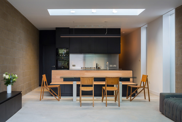 View of dining area with kitchen in the background Mustard Architects Industrial style dining room